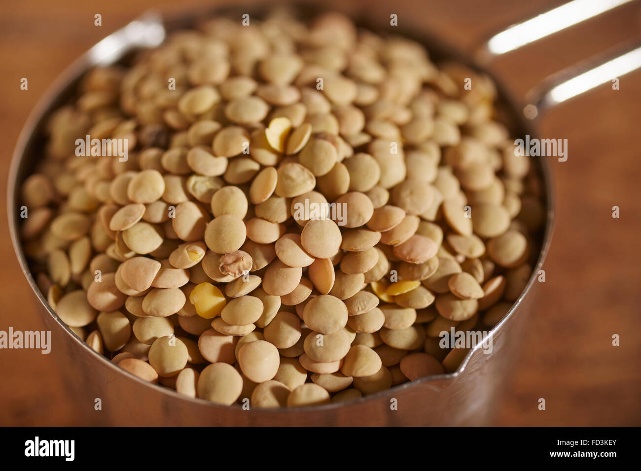 A cup of dried brown lentils Stock Photo