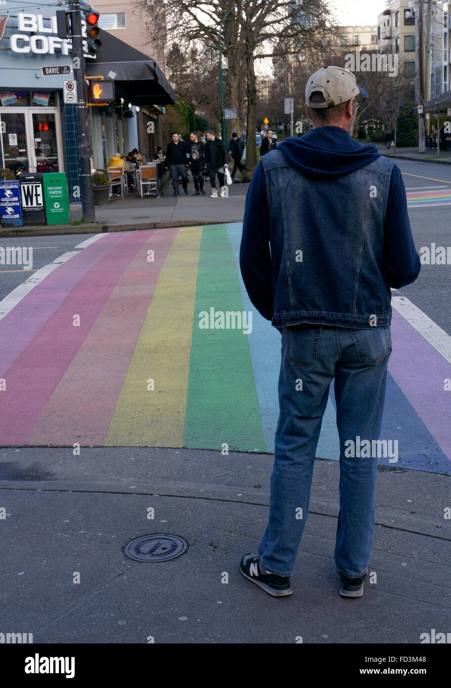 Man waiting to use the rainbow crosswalk symbolic of gay pride in the downtown West End of Vancouver, BC, Canada - Stock Image