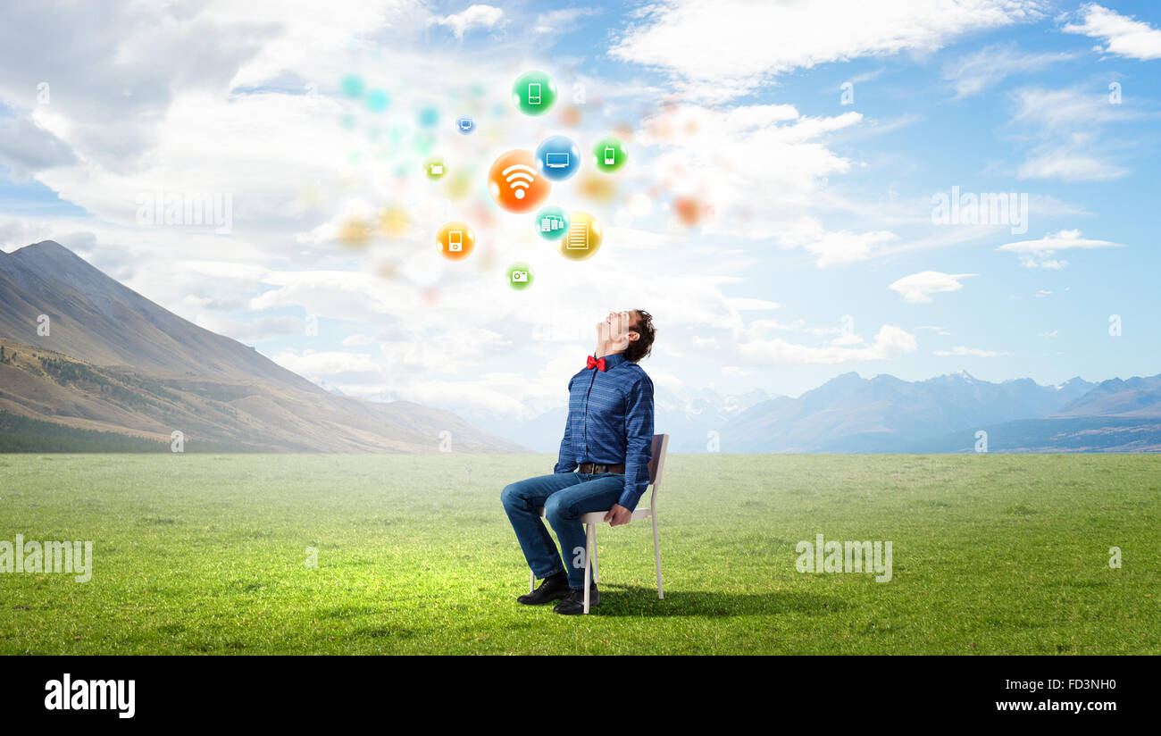 Young funny guy sitting in chair and looking upwards - Stock Image