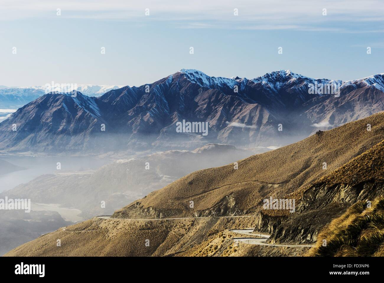 Windy road along the mountain range to Treble Cone Ski Resort, New Zealand. - Stock Image