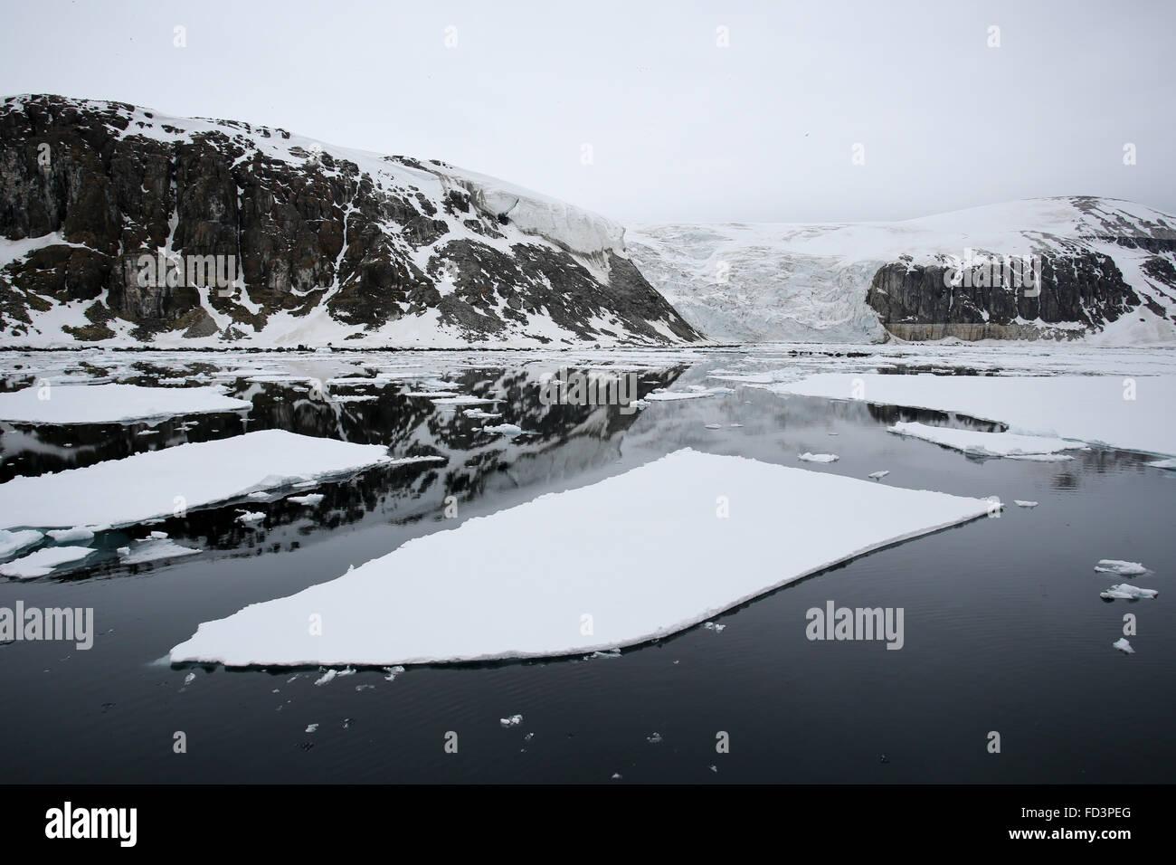 Svalbard, Spitsbergen, Alkefjellet. Glacier, snow covered cliffs and sea ice. - Stock Image