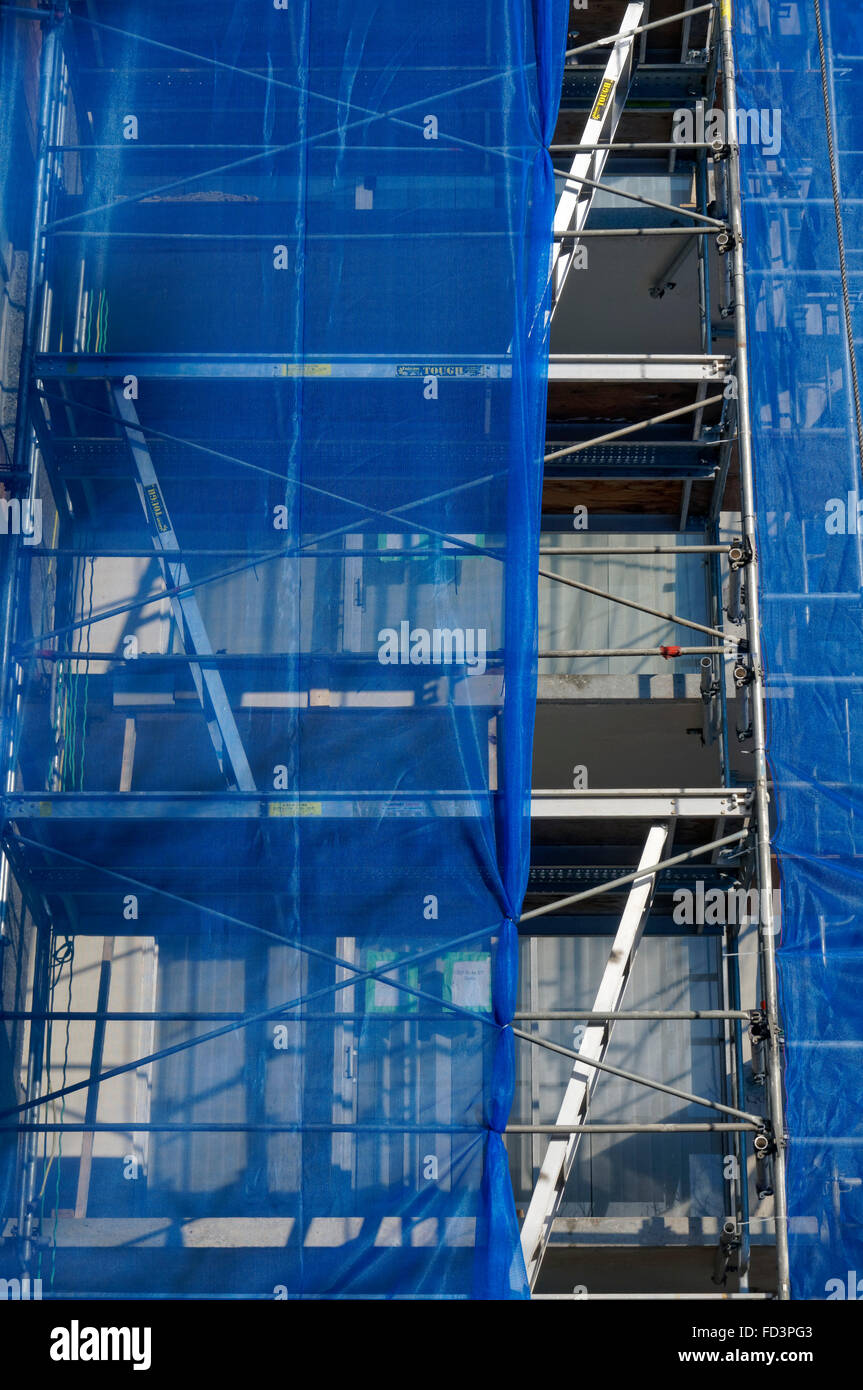 Staggered ladders at a building construction site - Stock Image
