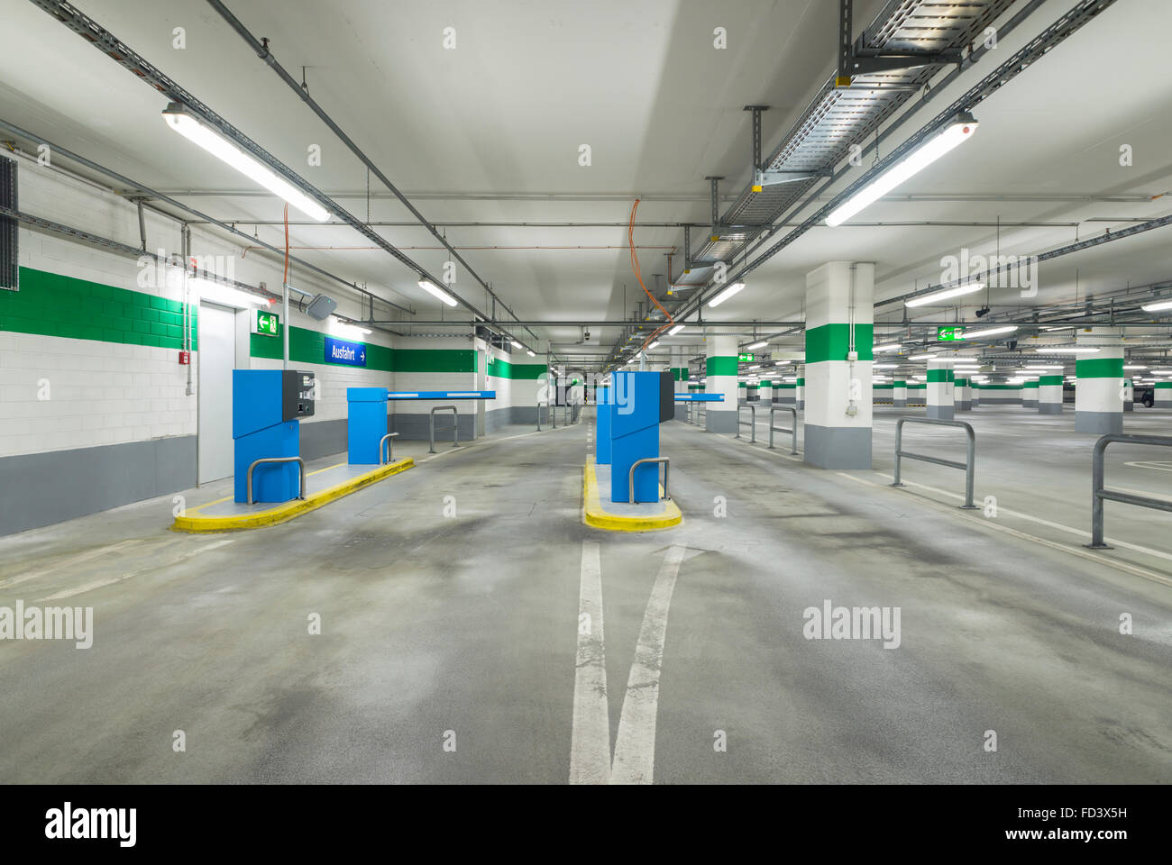Entrance lane of a parking garage with barrier and ticket machines - Stock Image
