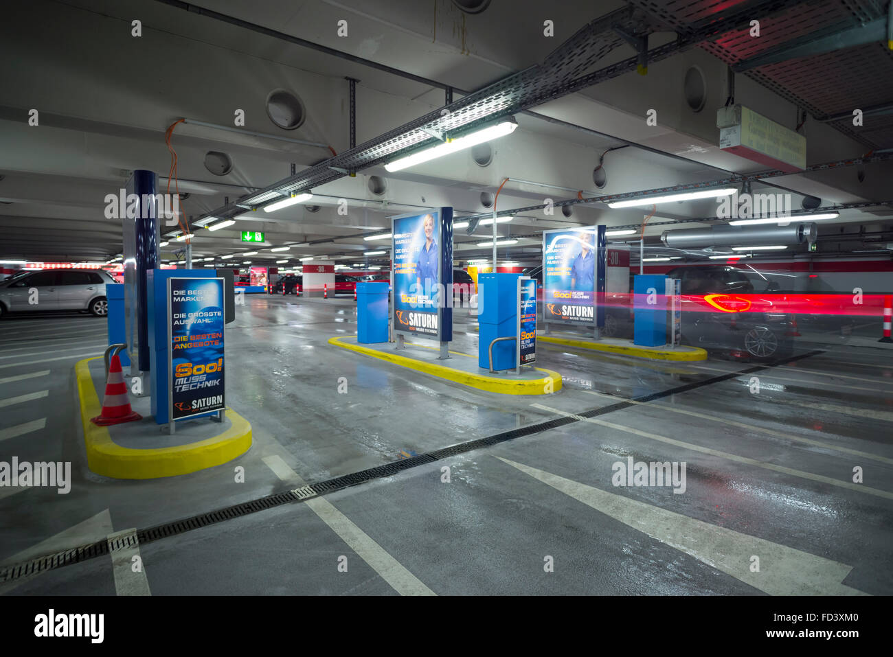 Entrance lane of a parking garage with barrier, ticket machines and advertisement boards - Stock Image