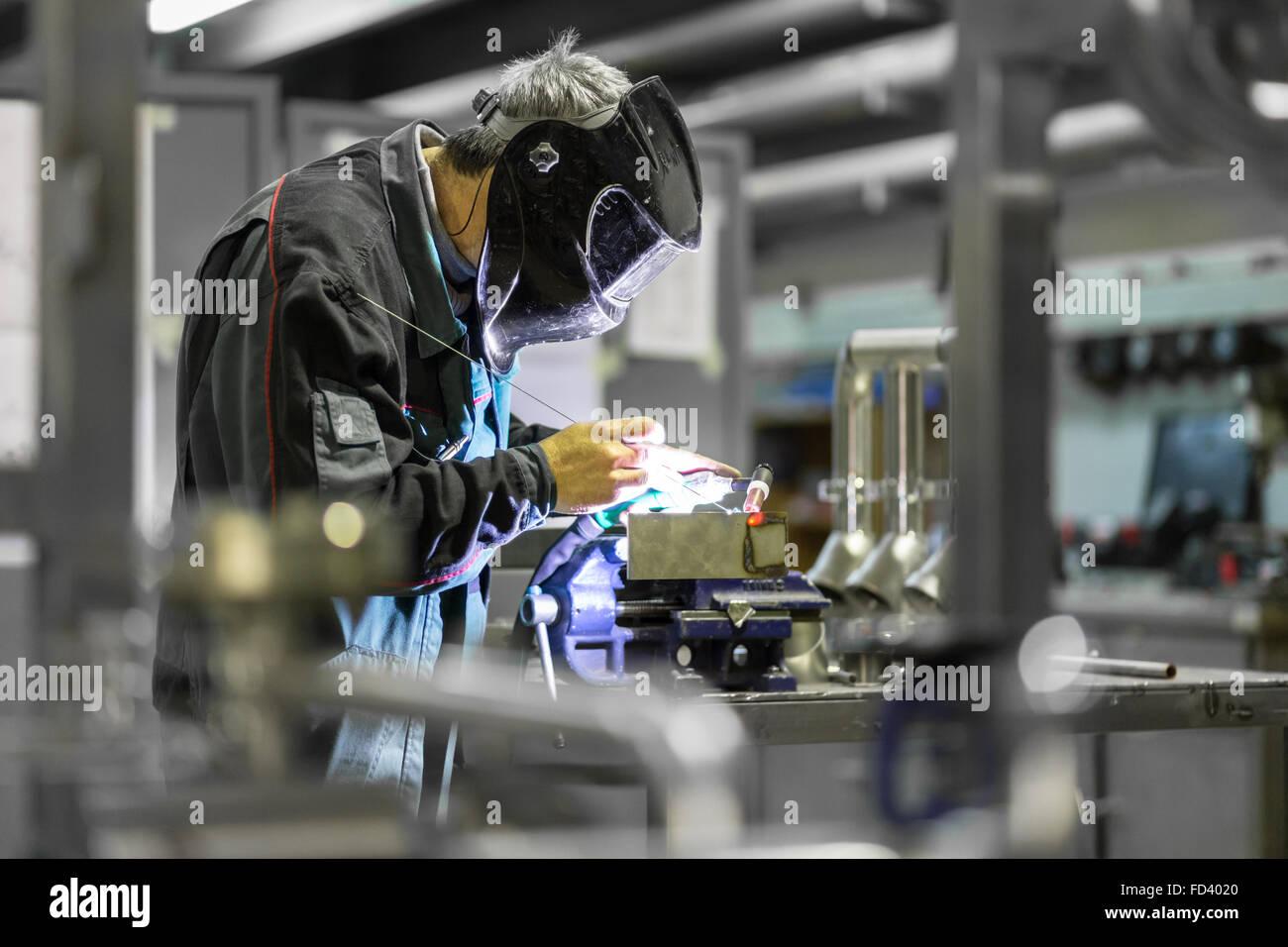 Industrial worker welding in metal factory. - Stock Image