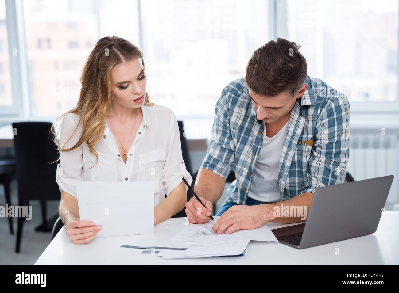 Concentrated pensive woman and man working and discussing project and using laptop in the office - Stock Image