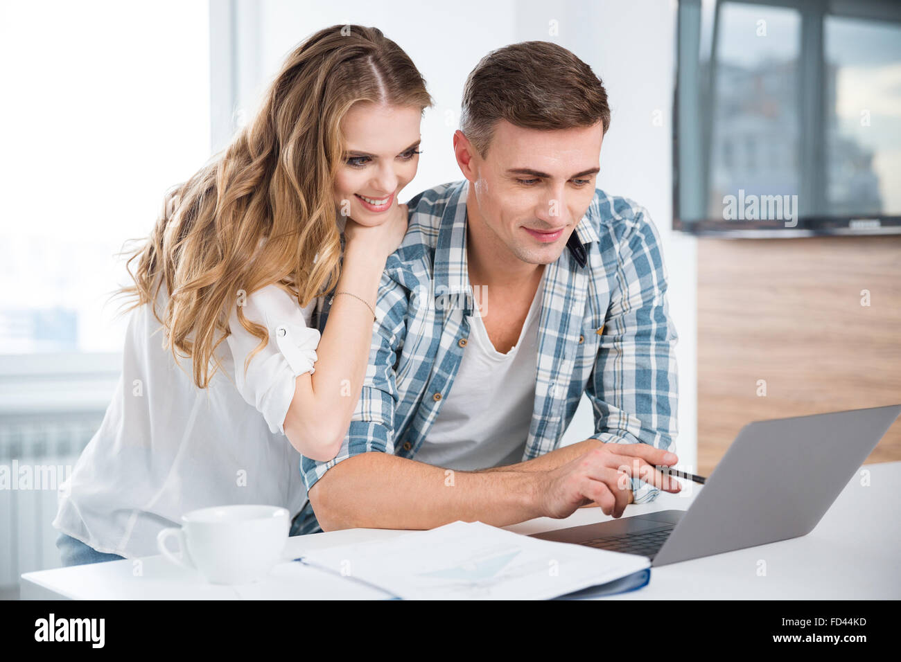 Beautiful couple using laptop and working together at home - Stock Image