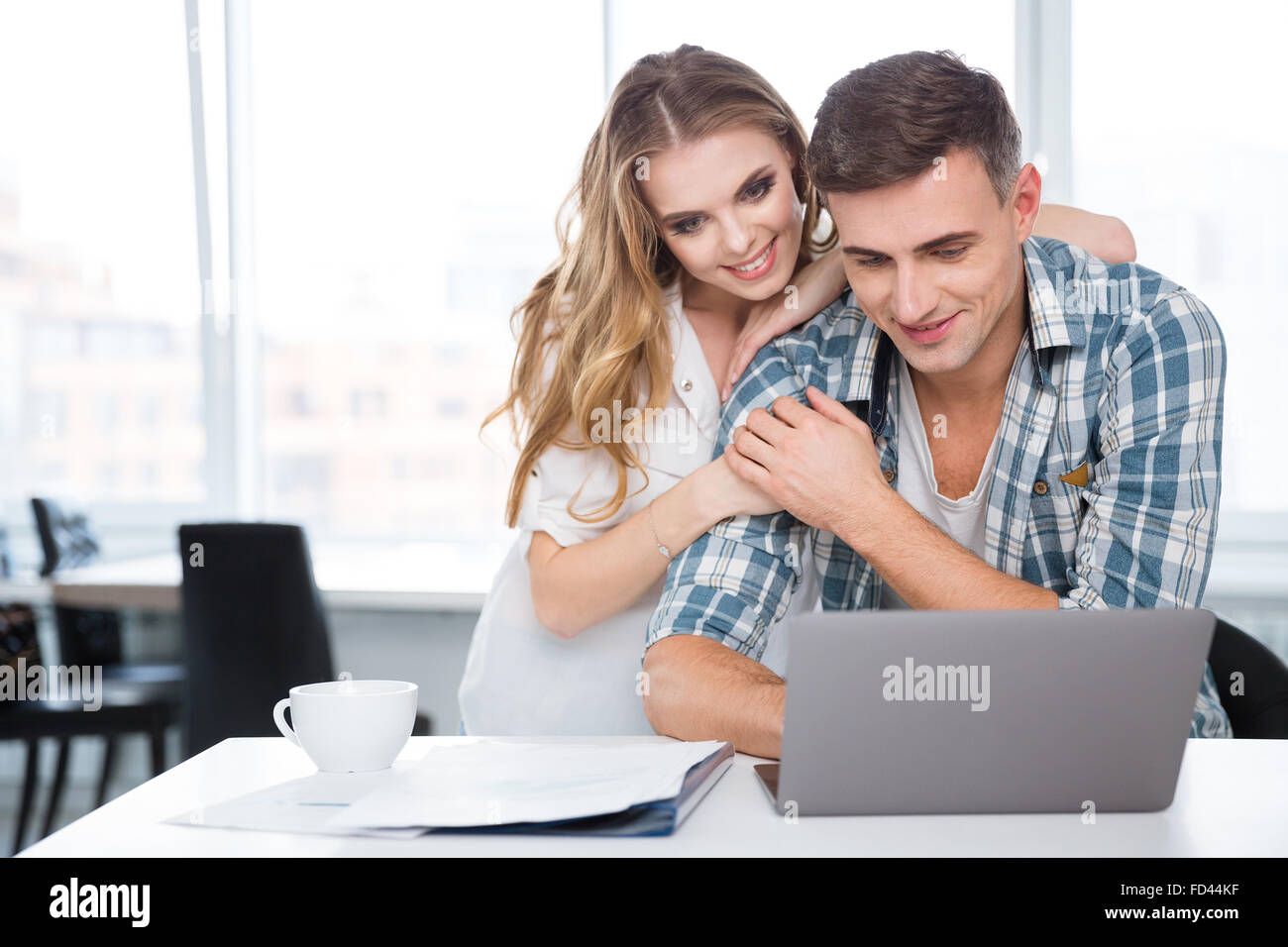 Happy beautiful couple using laptop together sitting at the table at home - Stock Image