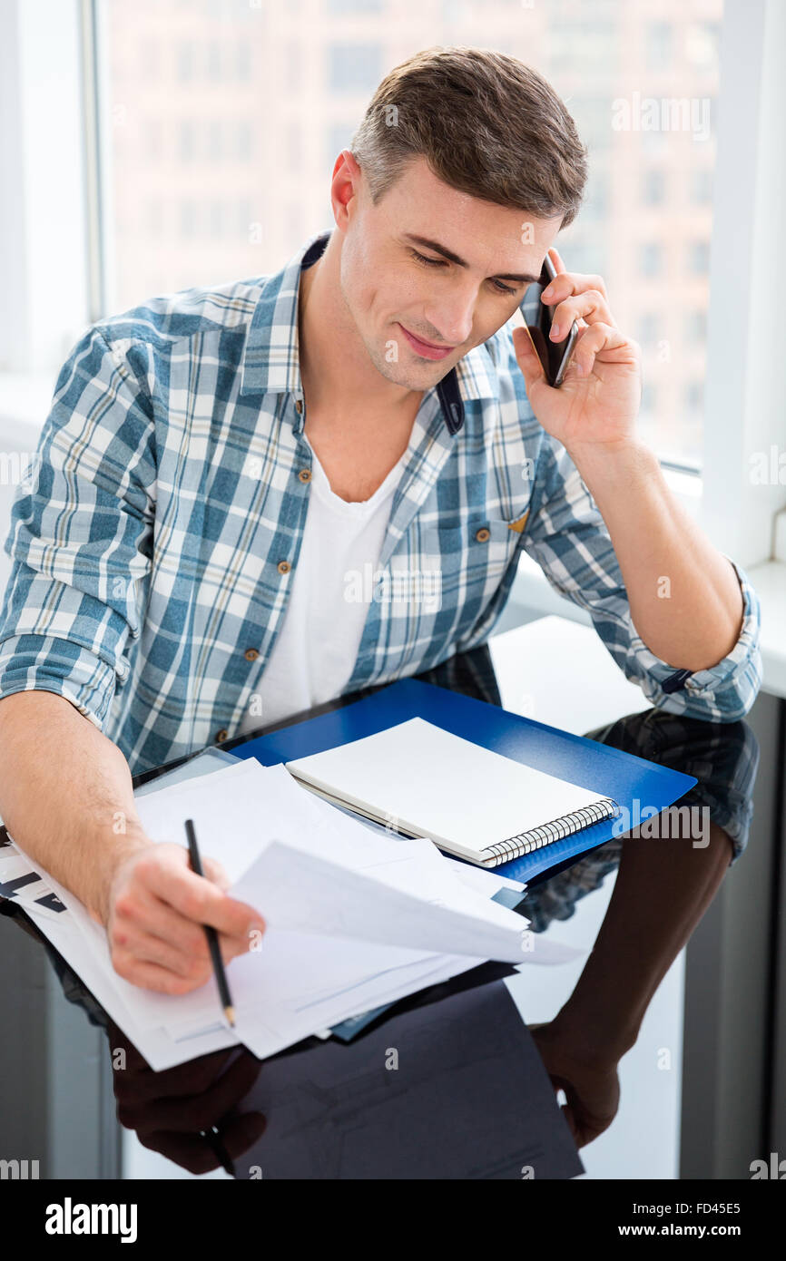 Confident man in checkered shirt sitting at the table with bills and talking on cell phone Stock Photo