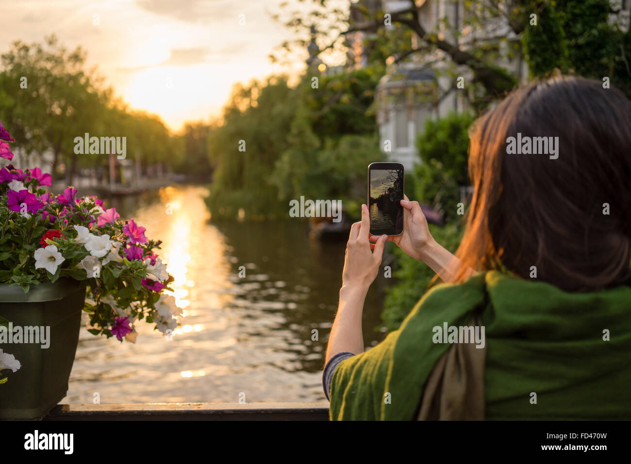 a tourist young women  in Amsterdam take pictures at a beautiful sunset on a bridge  tourist young women  in Amsterdam - Stock Image