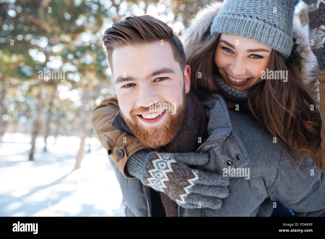 Smling beautiful couple walking in winter park and looking at camera - Stock Image