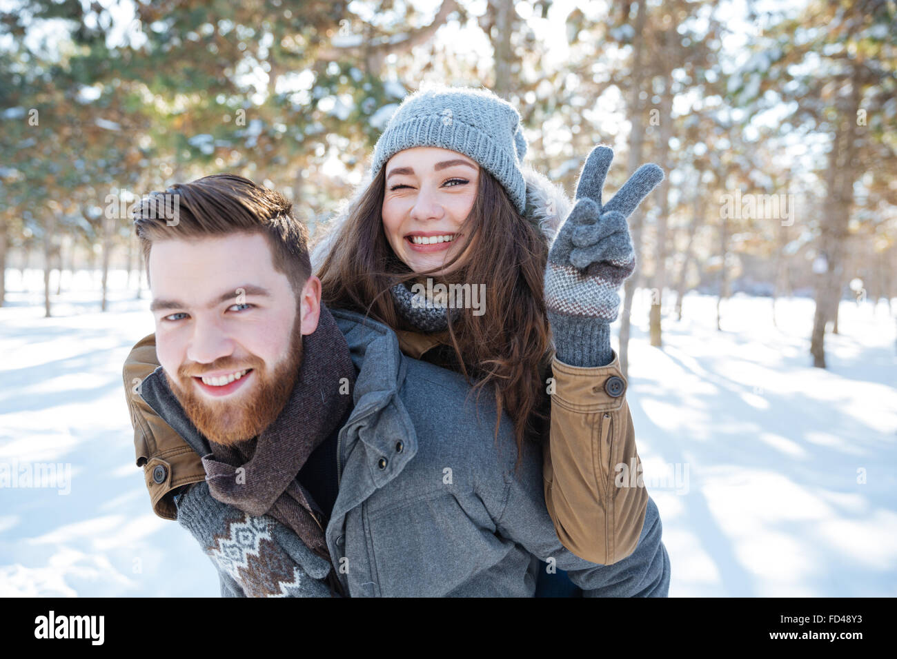 Happy young couple walking in winter park and showing victory sign at camera - Stock Image