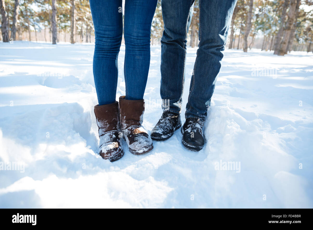 Closeup portrait of a male and female legs in jeans standing in winter park Stock Photo