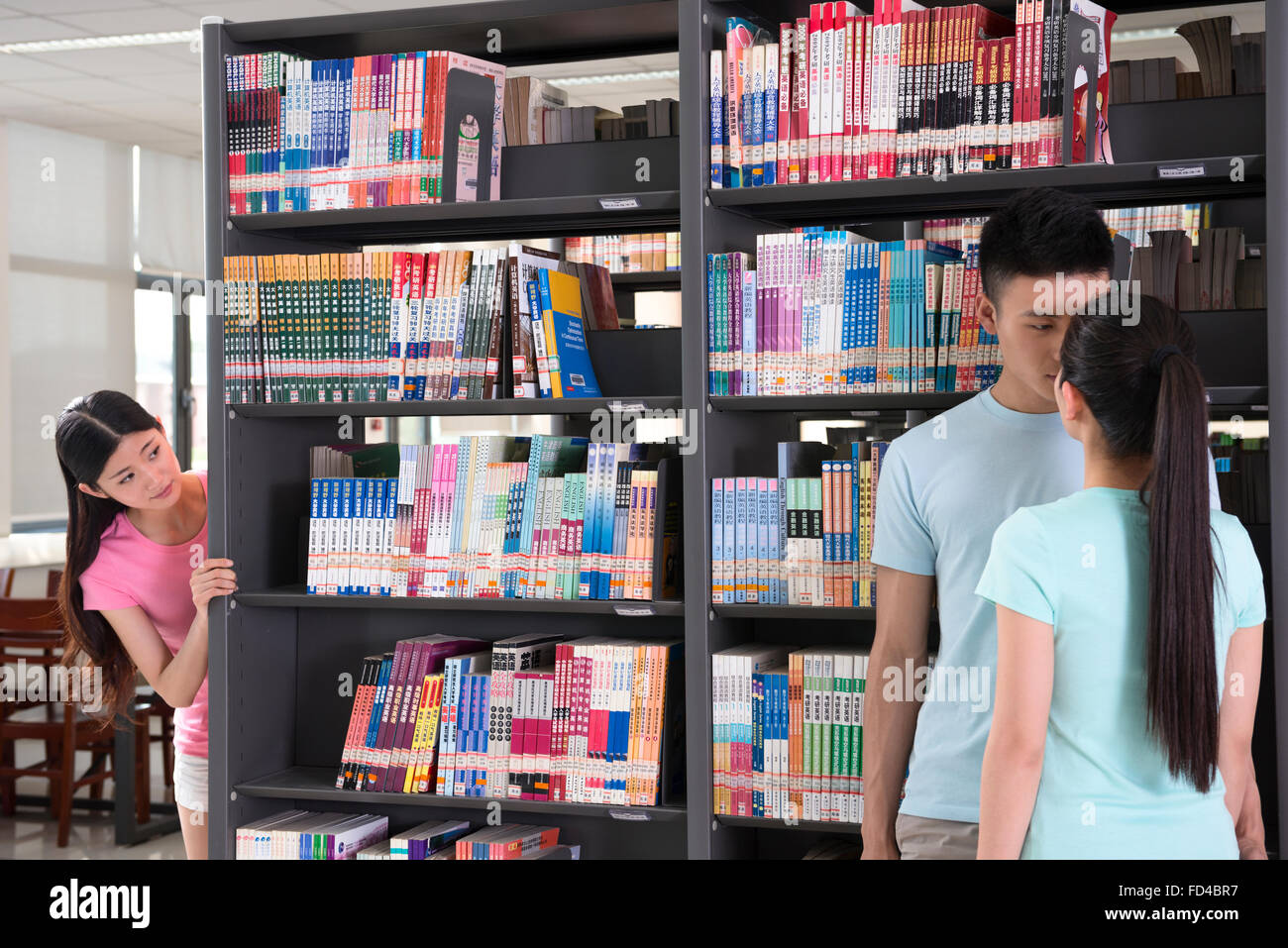 Unfaithful man caught cheating in library - Stock Image