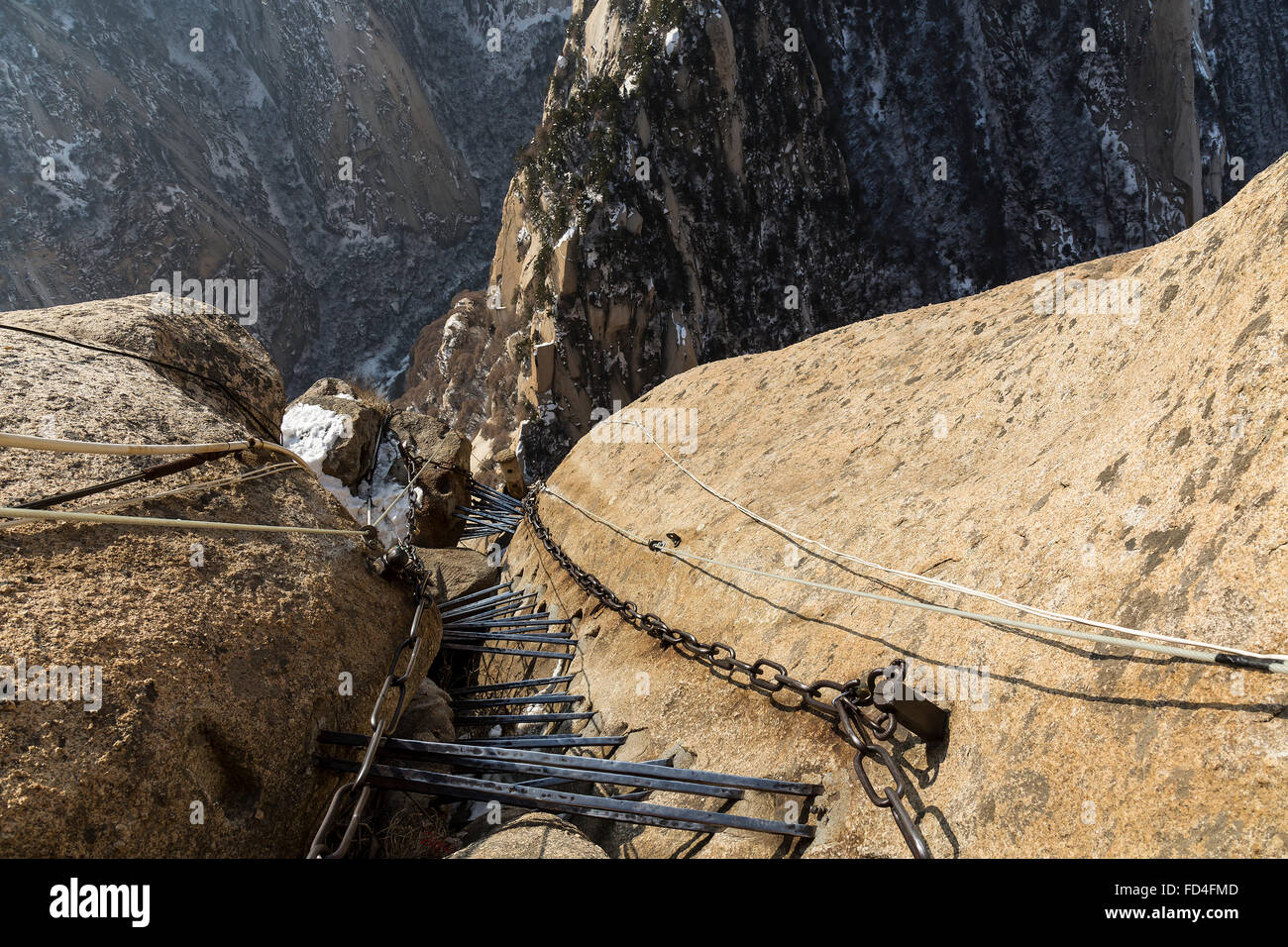 Chains and metal ladder going down at the South Peak of Huashan mountain. - Stock Image