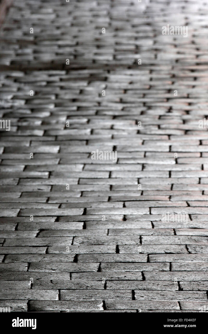 Old red hexagonal tile floor in a church. - Stock Image