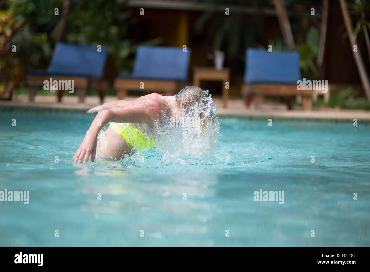 Side View Of Woman Flipping Hair In Swimming Pool - Stock Image
