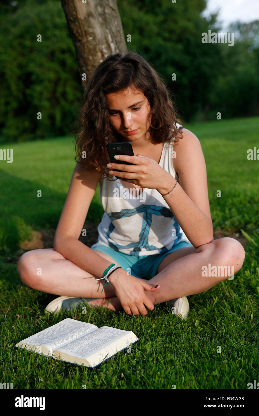 Teenager using a cell phone. - Stock Image