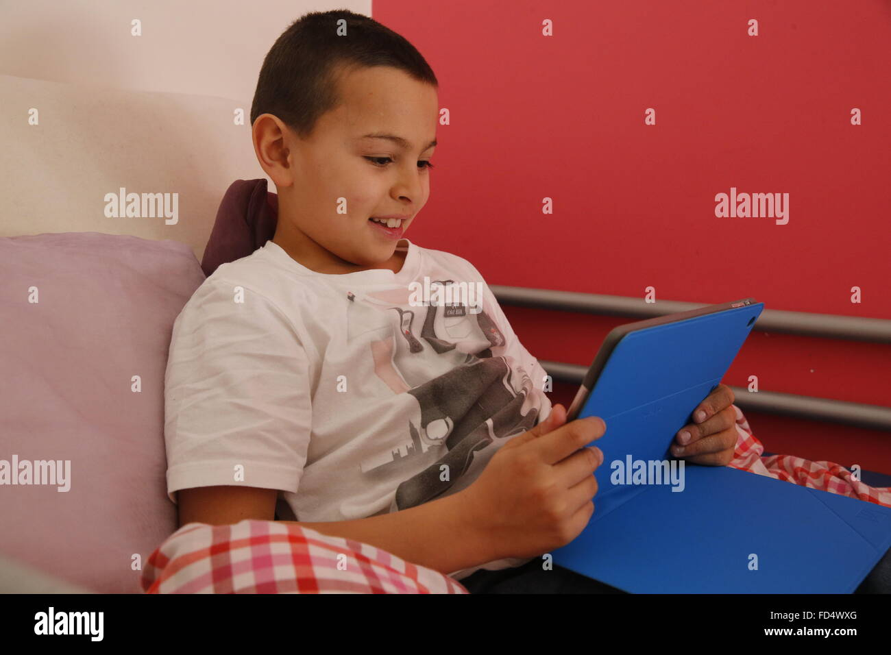 9-year-old boy using a digital tablet in his room. - Stock Image