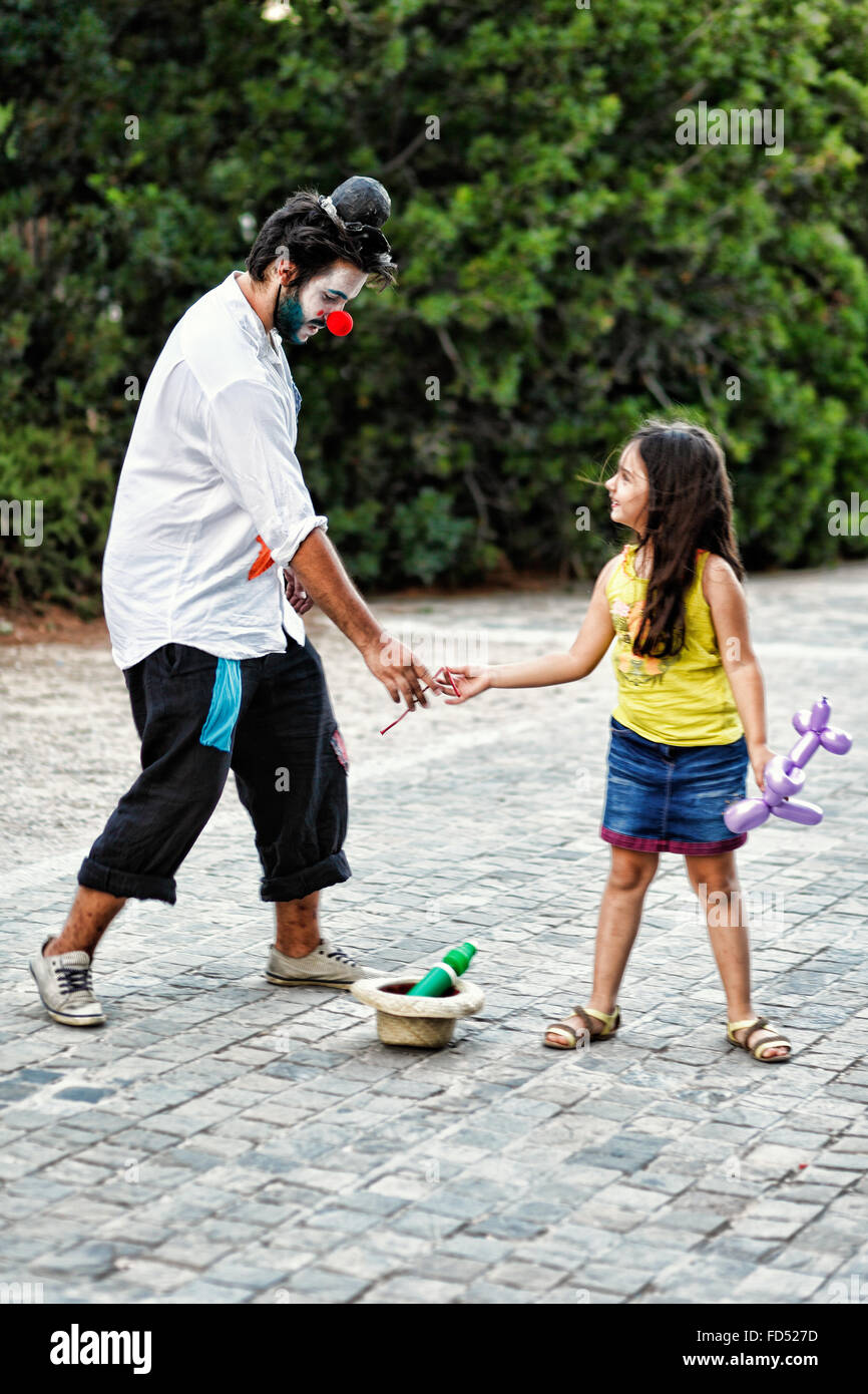 A clown gives balloon to a little girl in the streets of Athens, Greece - Stock Image