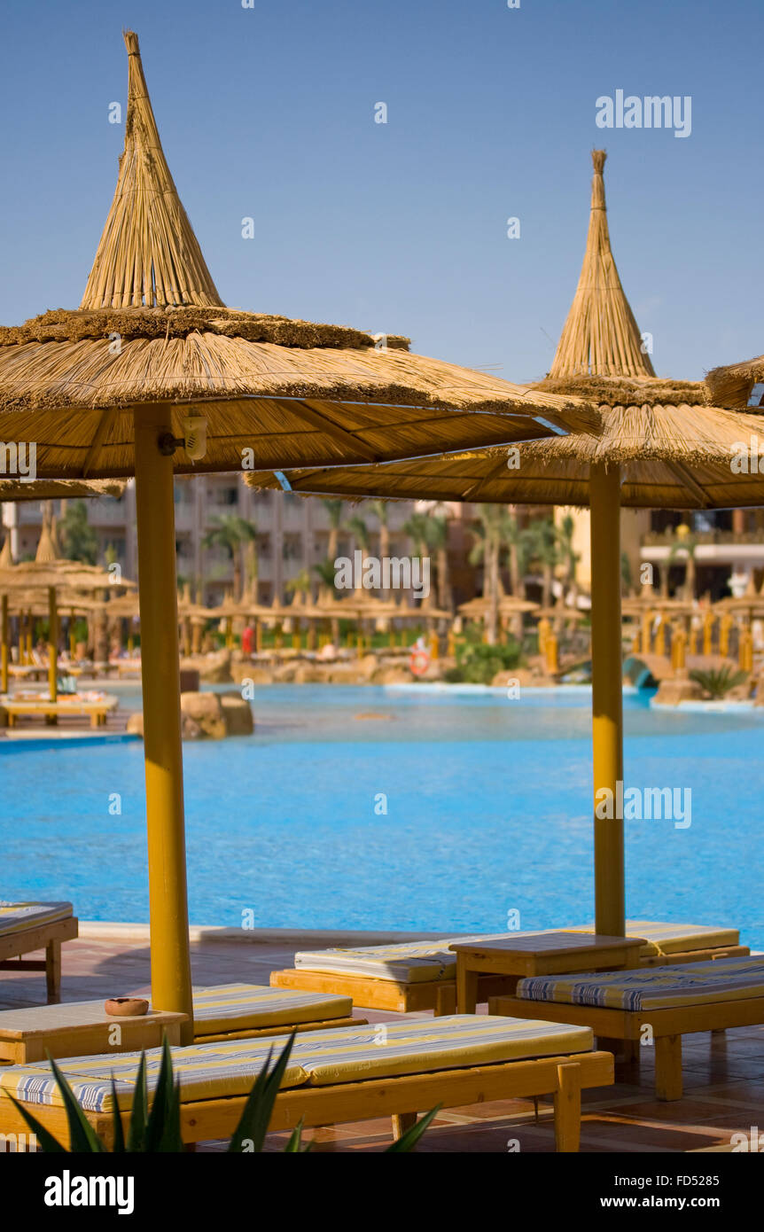 Resort hotel with poolside loungers. - Stock Image