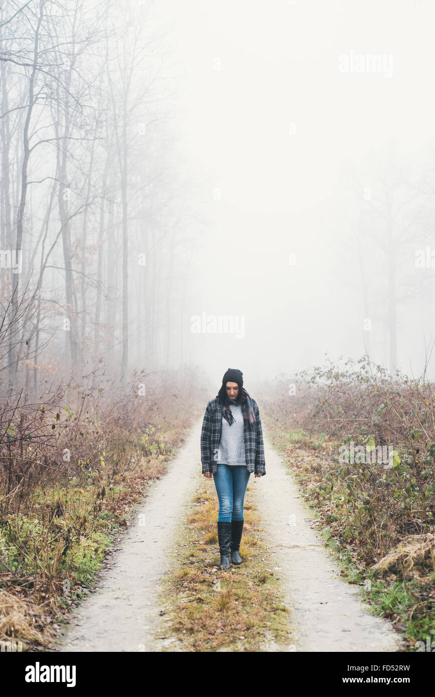 Woman having a walk in misty forest - Stock Image