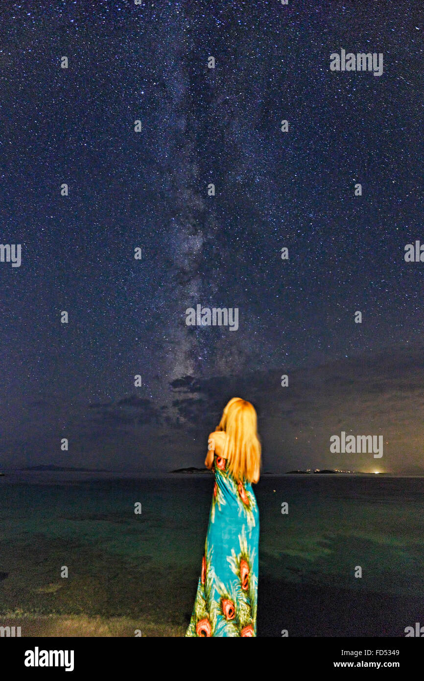 A woman looking at the Milky Way on the beach - Stock Image