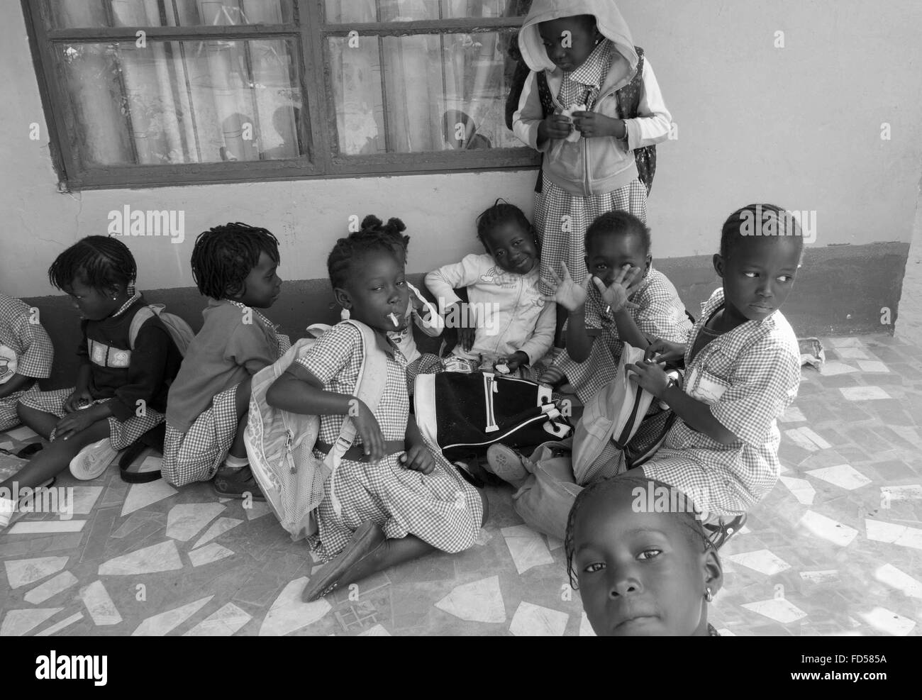 Lunch break for black infant children at a charity run school in the back streets of Kololi Gambia - Stock Image