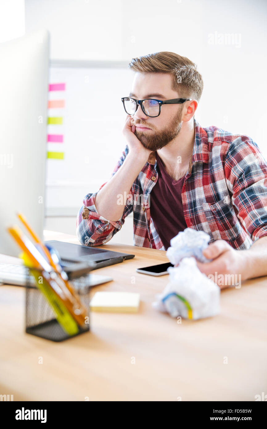 Thoughtful young man with beard in plaid shirt working and crumpling paper in the office - Stock Image