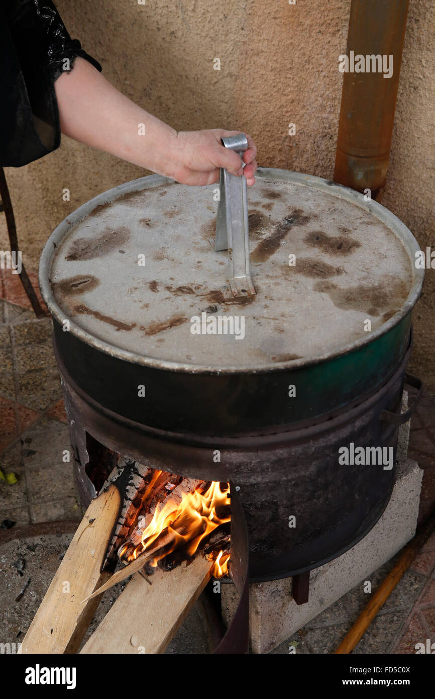 Palestinian woman using a hot stone oven. - Stock Image