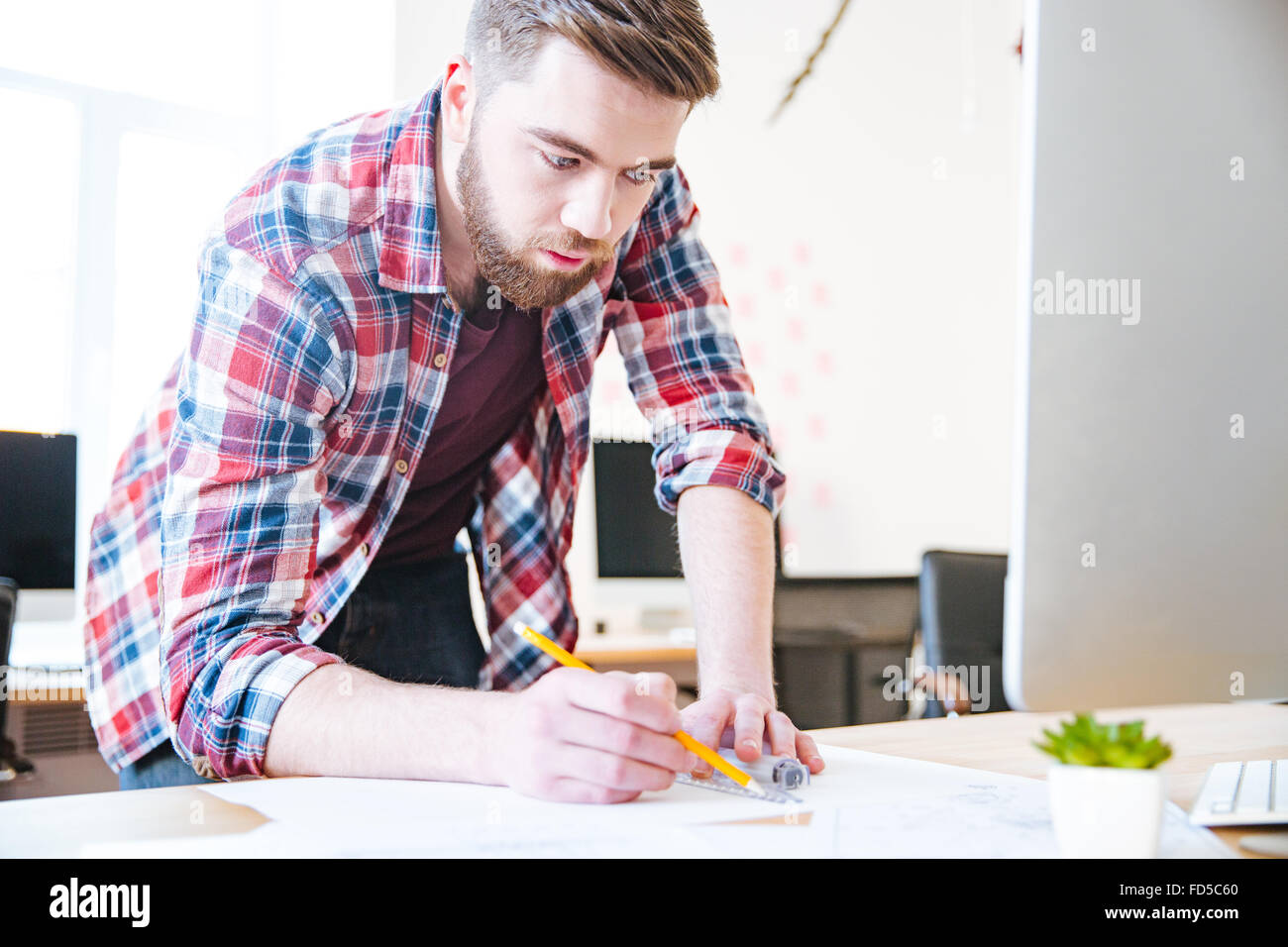 Concentrated handsome man in checkered shirt working and drawing blueprint with ruler and pencil - Stock Image