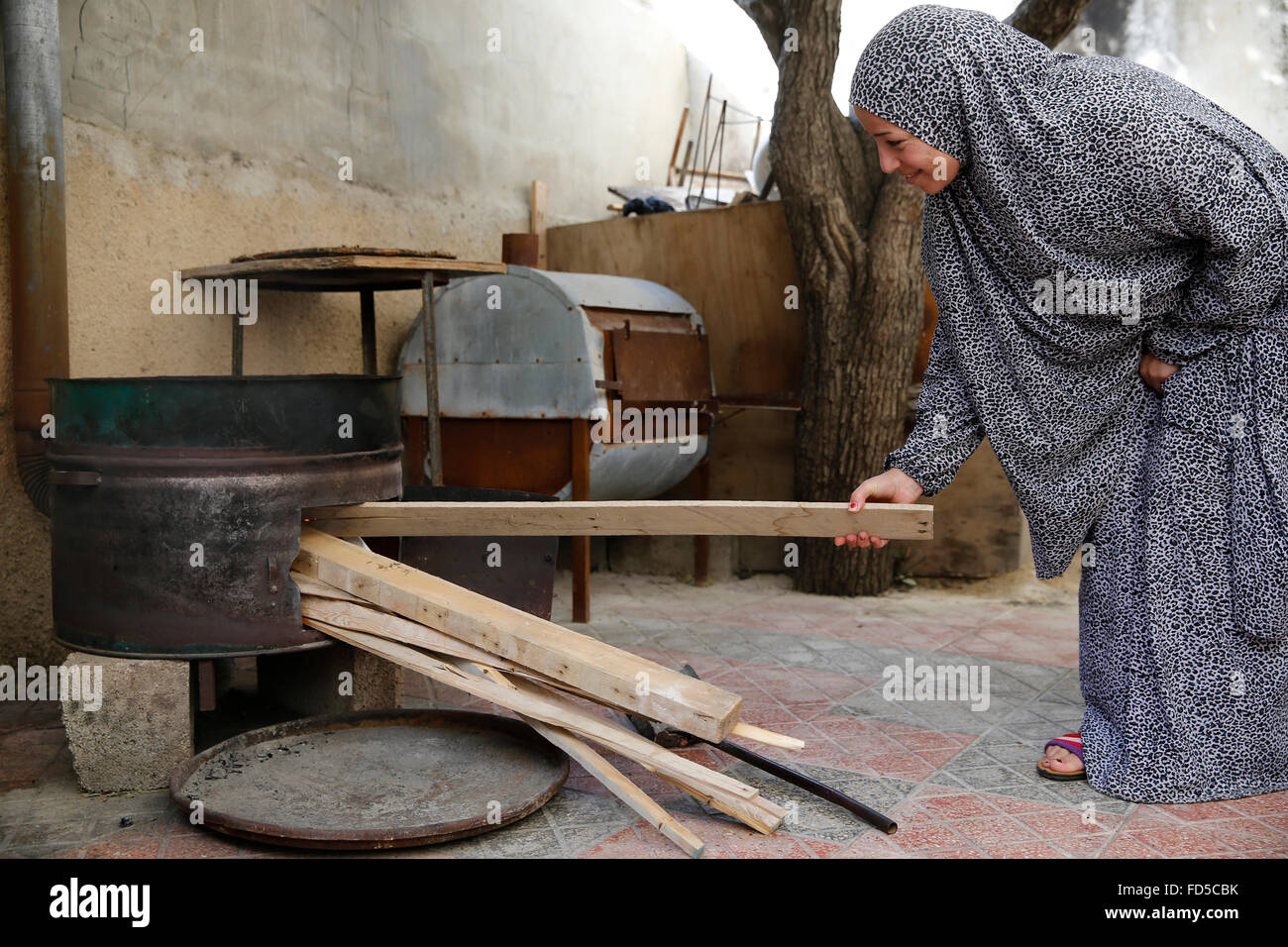 Palestinian woman loading wood into an oven. - Stock Image