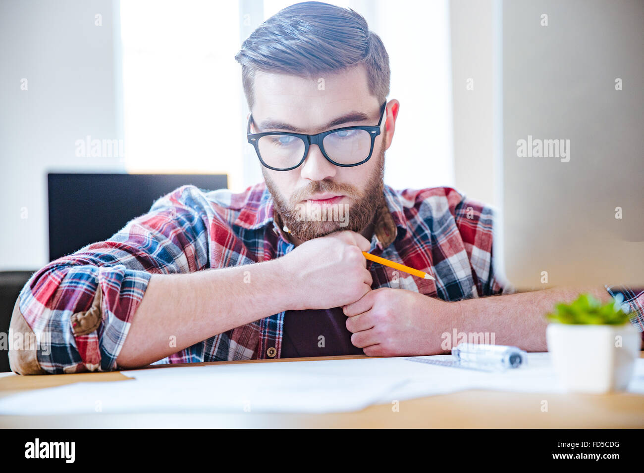 Portrait of pensive bearded young engineer in glasses sitting at the table and creating blueprint - Stock Image