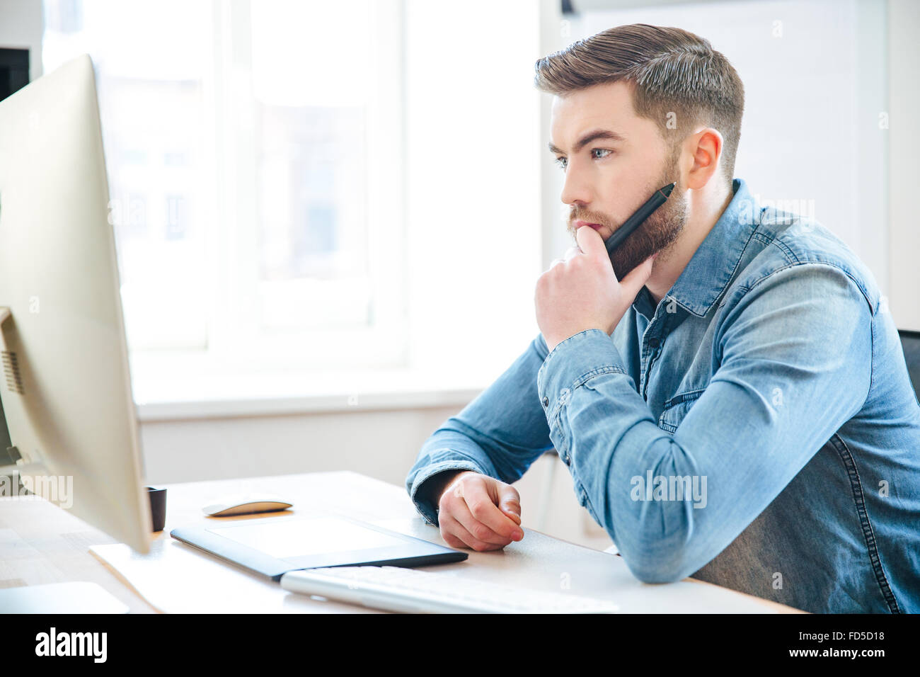 Pensive attractive bearded male designer in jeans shirt thinking and making blueprints using pen tablet - Stock Image
