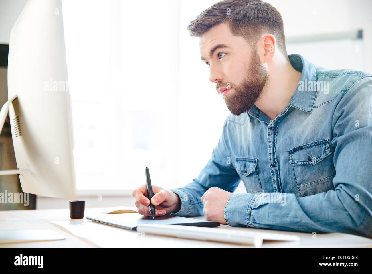 Concentrated handsome young designer with beard in blue shirt drawing using computer and graphic tablet in the office - Stock Image