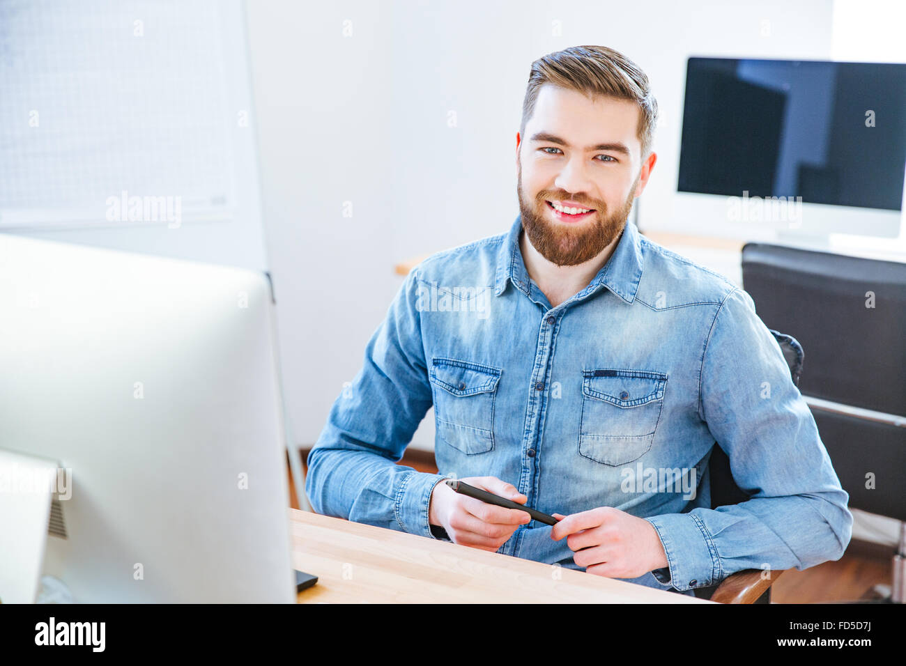 Cheerful handsome young designer with beard in blue shirt holding stylus and sitting at the table in office - Stock Image