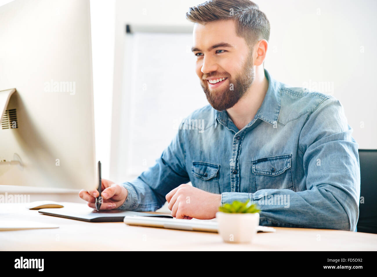 Happy attractive young male designer sitting in office and drawing on graphic tablet - Stock Image