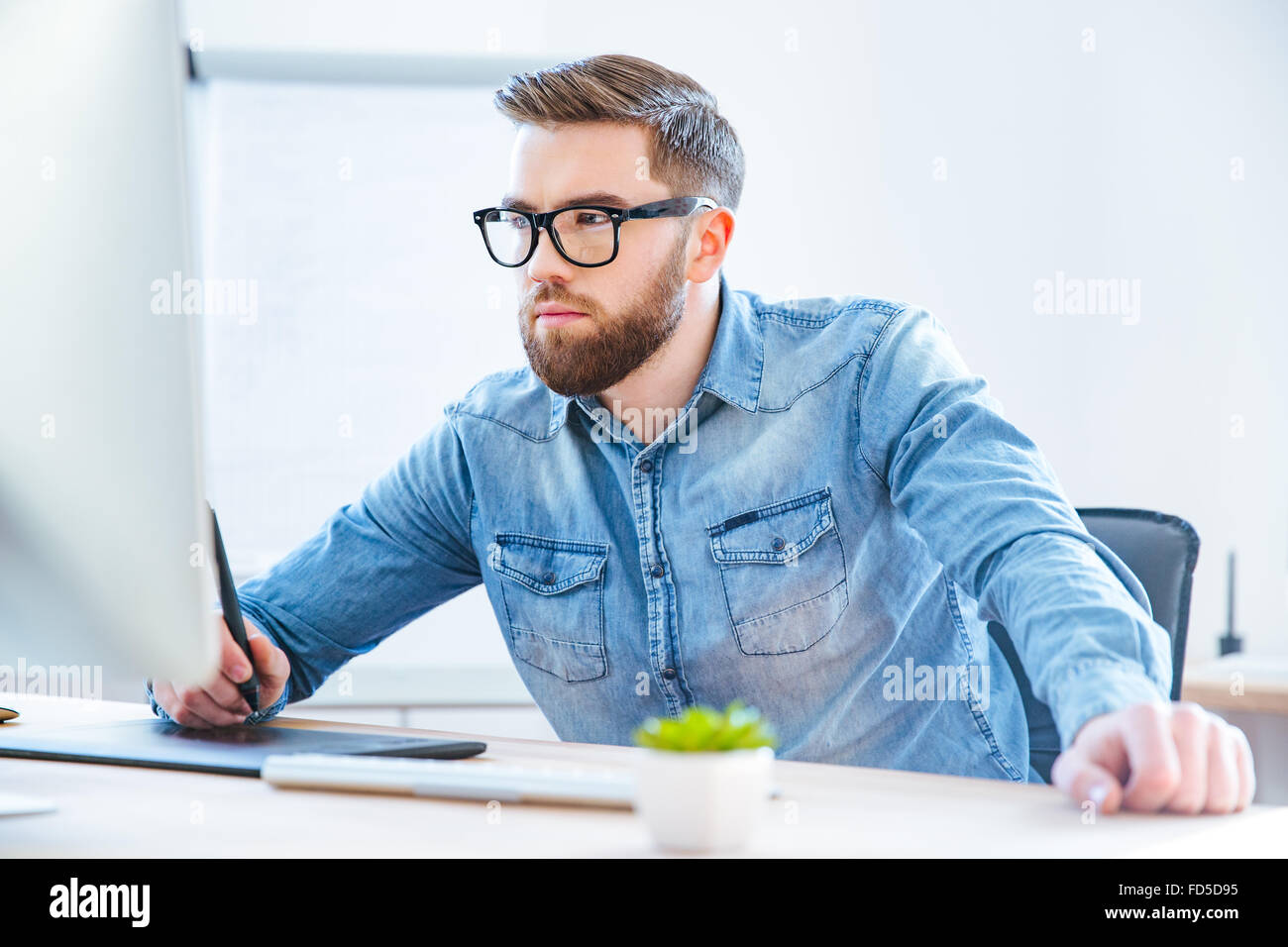 Serious concentrated young man designer drawing with graphic pen tablet using stylus in office Stock Photo