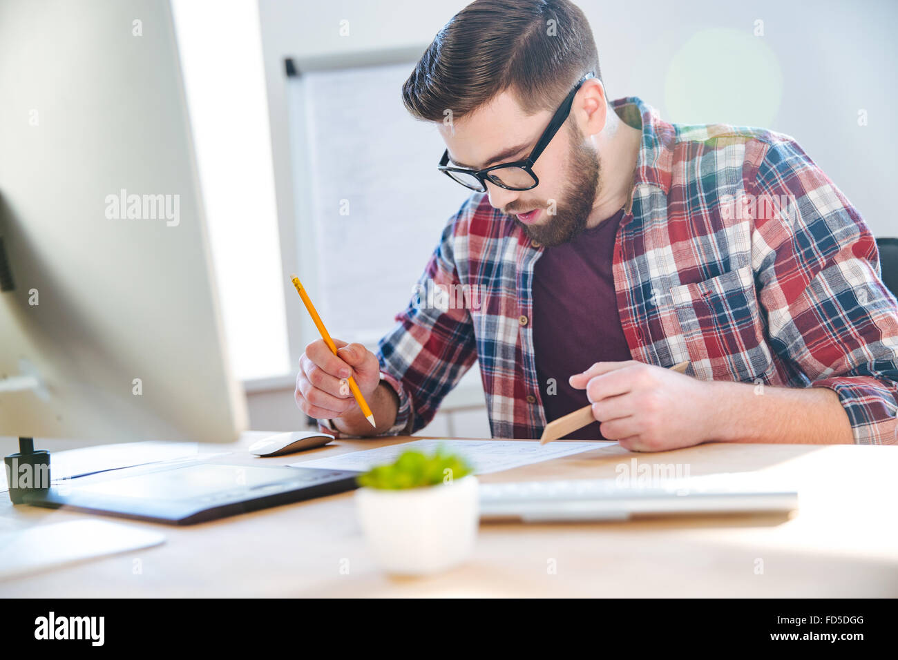 Handsome concentrated young man with beard working with blueprint using ruler and pencil in office - Stock Image