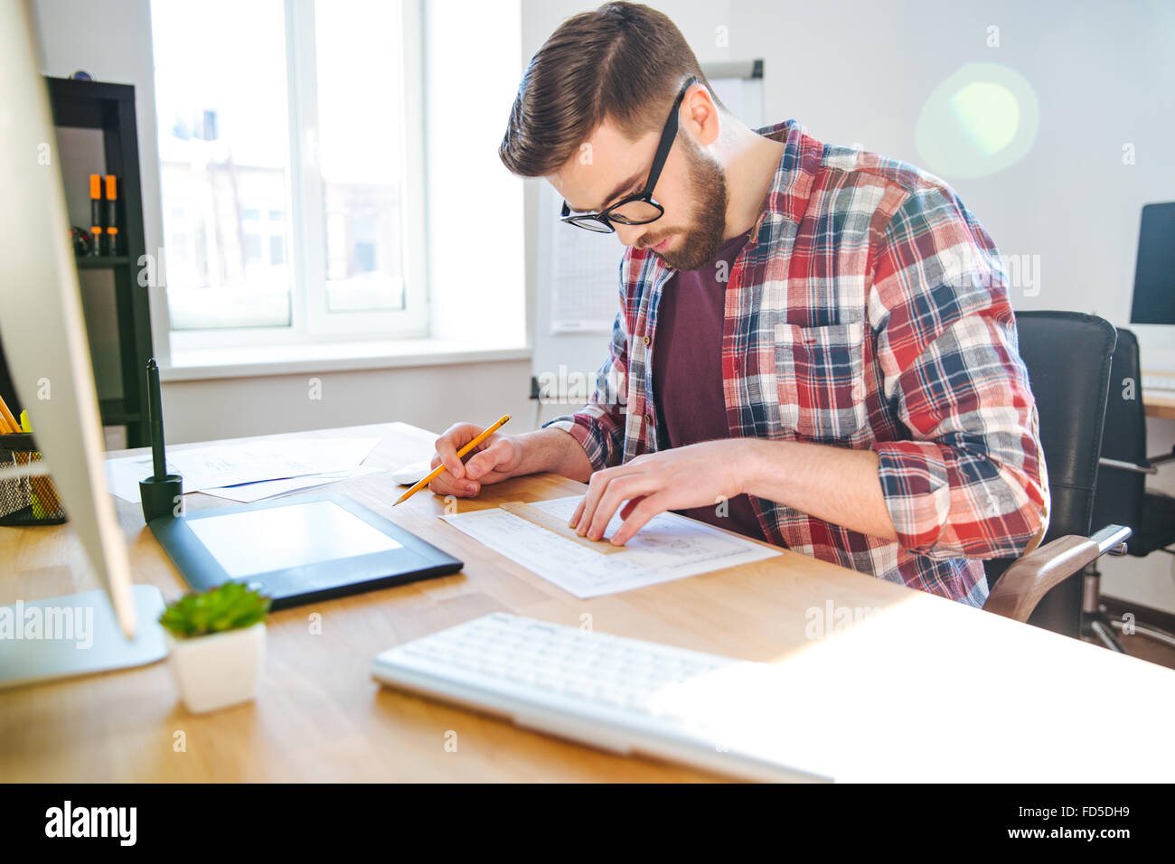 Portrait of young male designer in glasses sitting in office and making blueprint - Stock Image