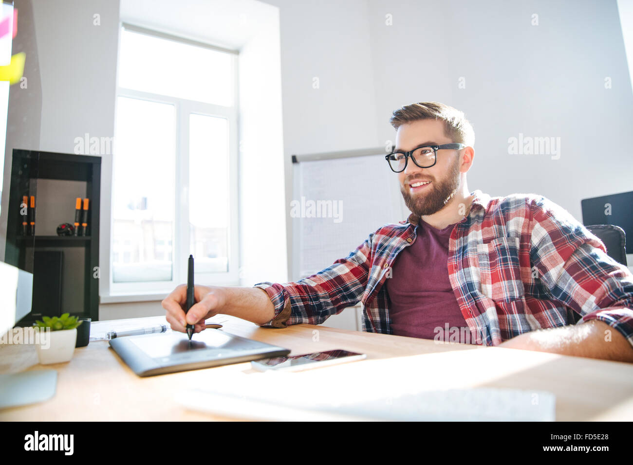 Smiling handsome young bearded designer in checkered shirt and glasses drawing and using graphic pen tablet and - Stock Image