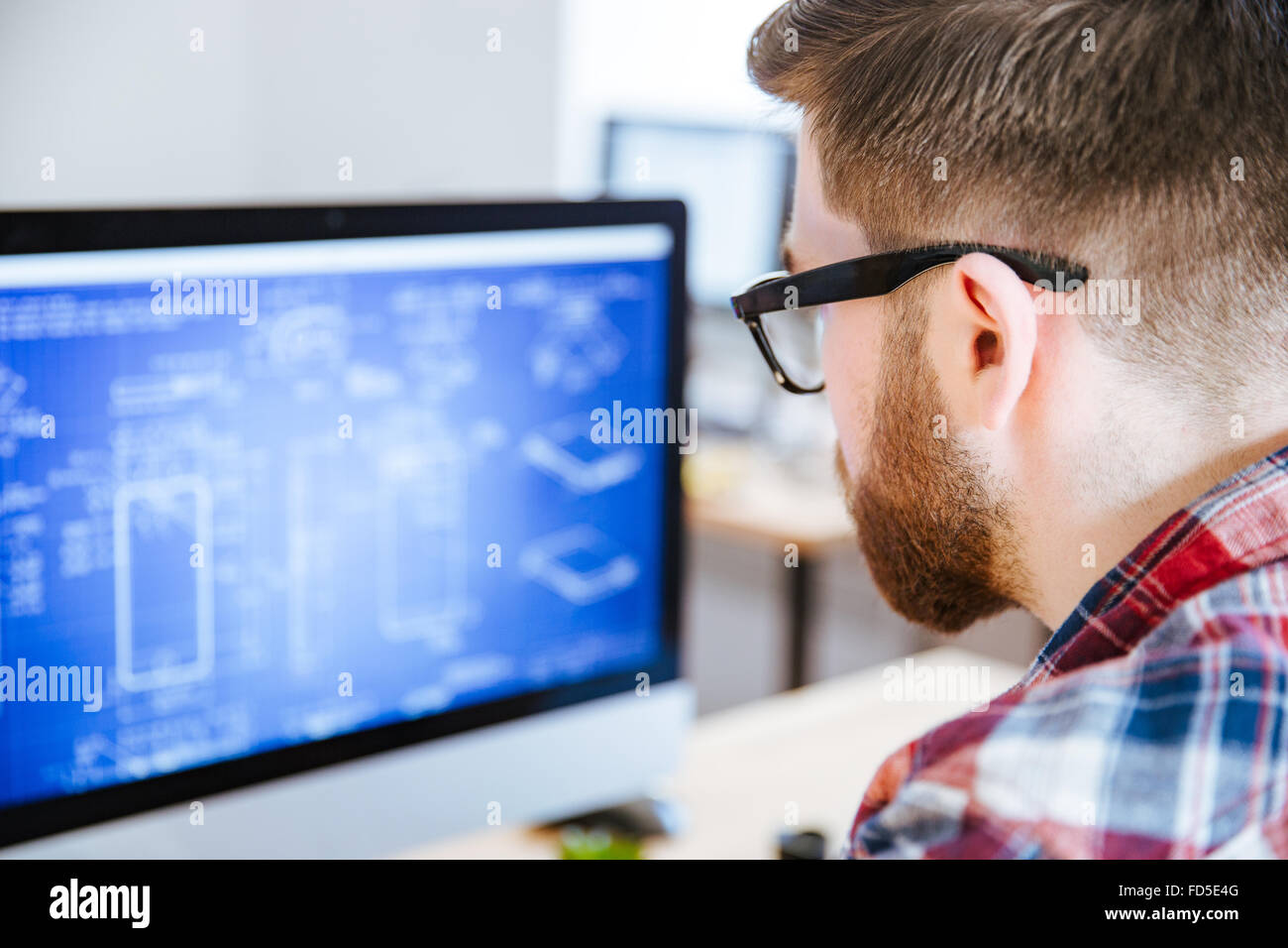 Closeup of young man in glasses with beard making blueprints on computer - Stock Image
