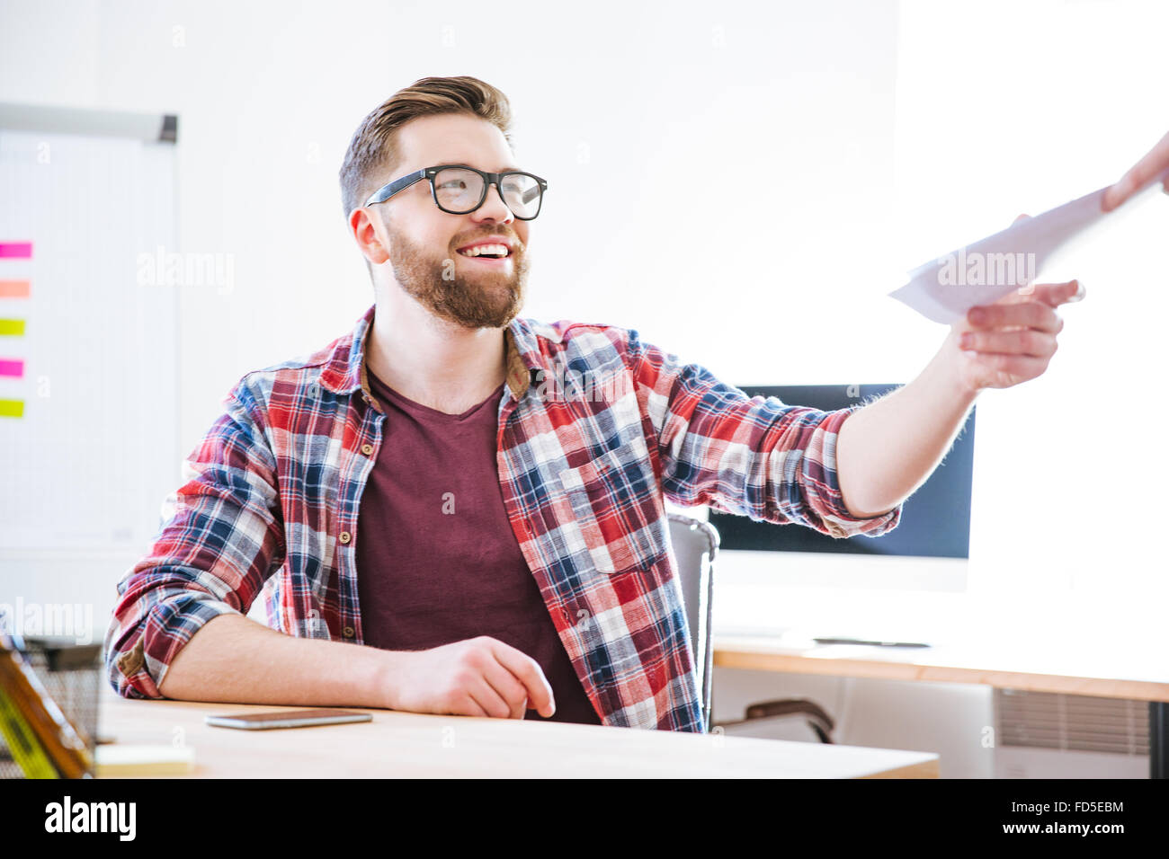 Cheerful attractive young man in checkered shirt siting on workplace and receiving documents - Stock Image