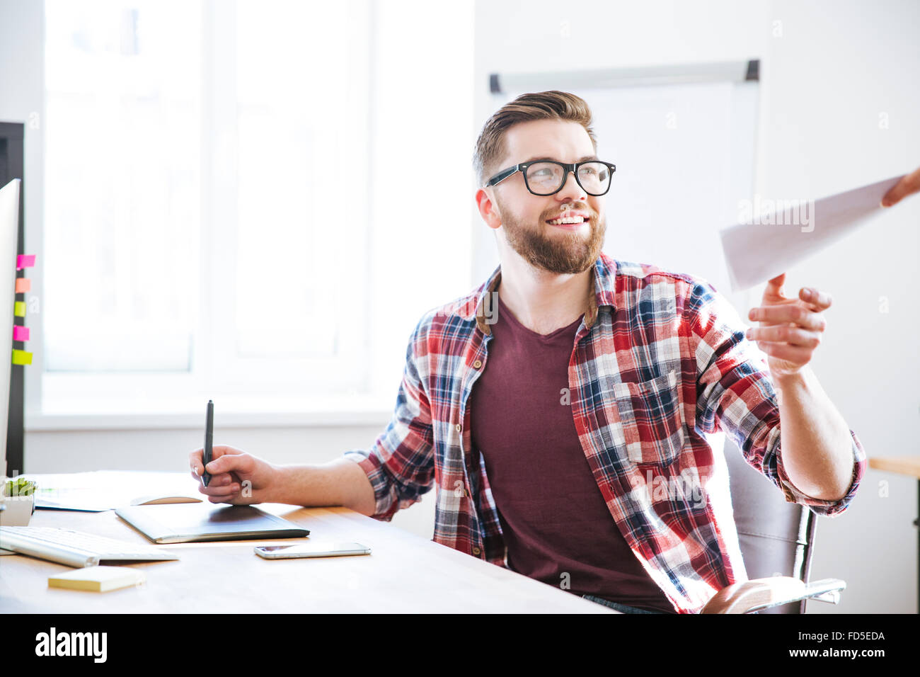 Happy handsome bearded designer using graphic pen tablet with stylus and receiving blueprints - Stock Image