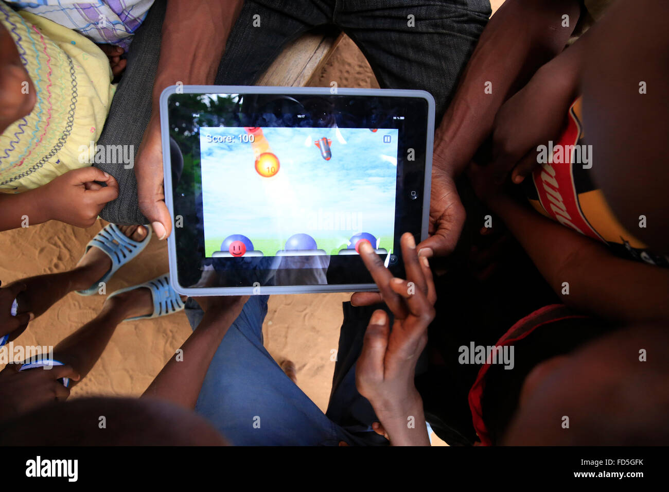 African children playing with a digital tablet. - Stock Image