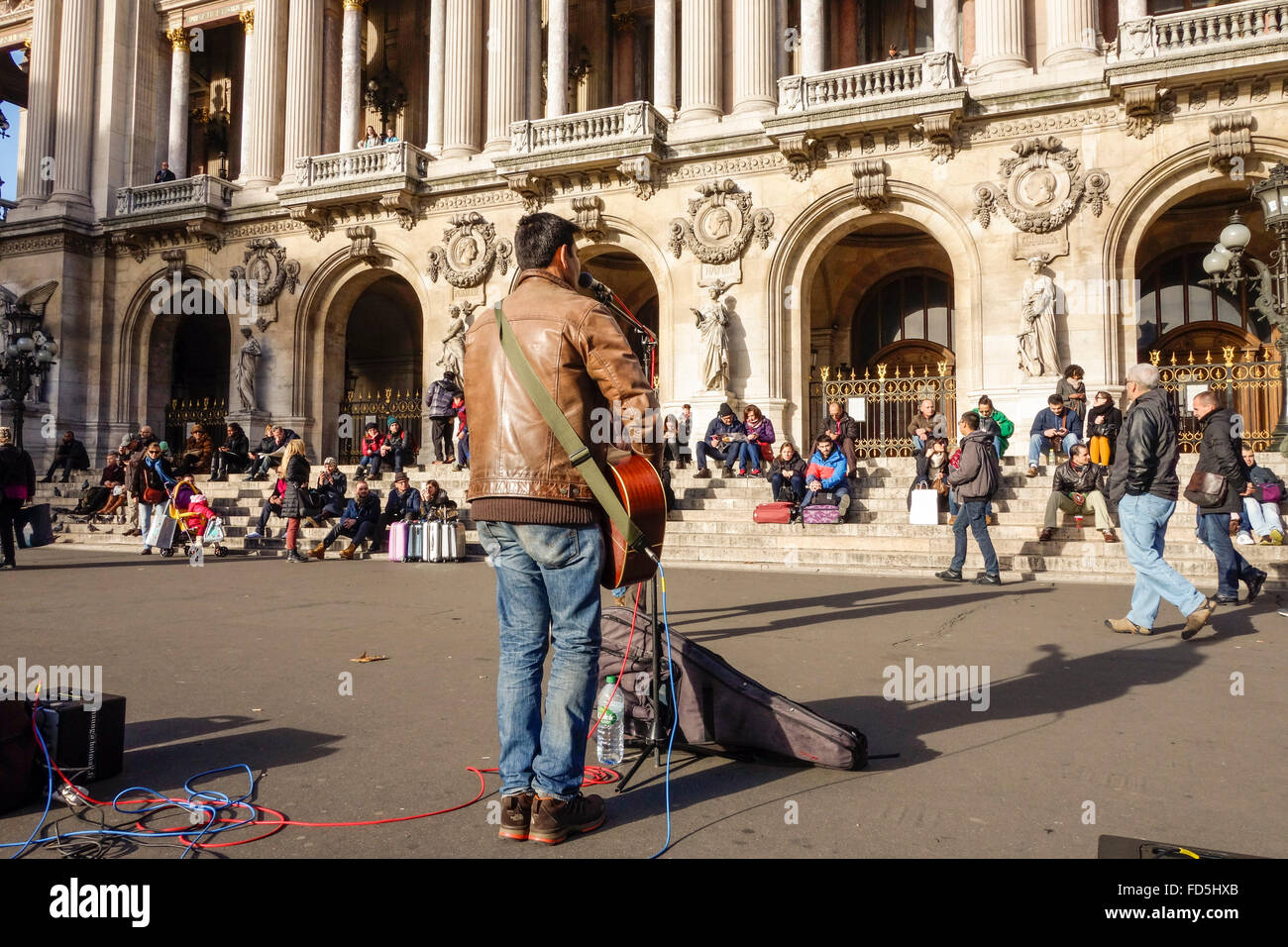 Street musician playing in front of the Palais Garnier, Opera House in Paris, France. - Stock Image