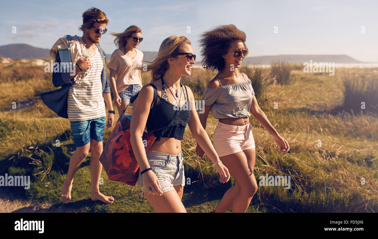 Portrait of group of friends going to on the beach. Mixed group of friends walking on the beach on summer day. - Stock Image