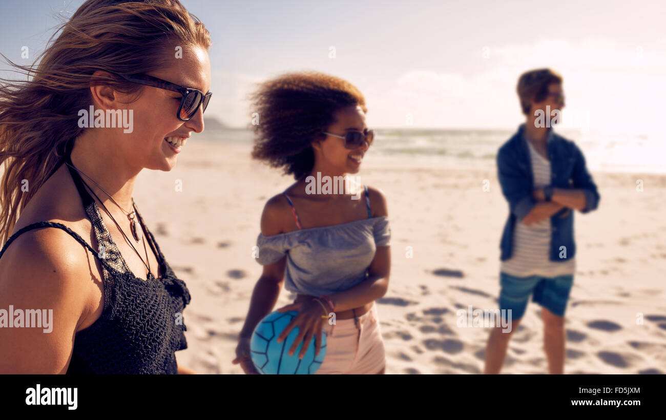 Young woman smiling and friends playing with volleyball on the beach. Young people enjoying summer vacation on the - Stock Image