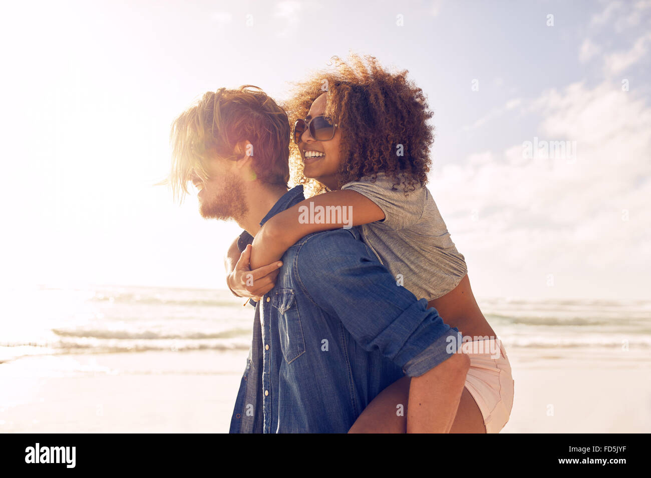 Side view portrait of young man carrying his girlfriend on his back at the beach. Boyfriends giving piggyback ride - Stock Image