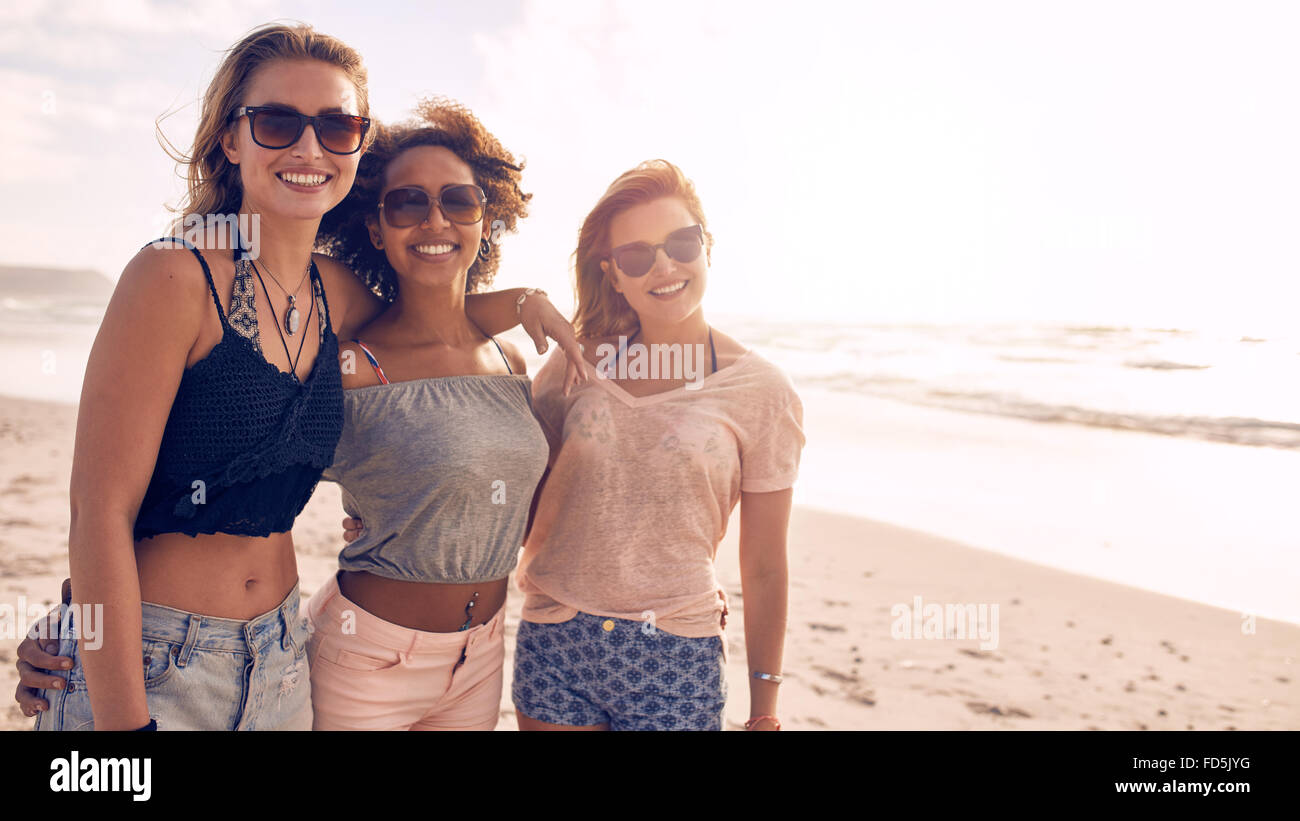 Portrait of three young female friends standing together on the sea shore looking at camera and smiling. Multiracial - Stock Image